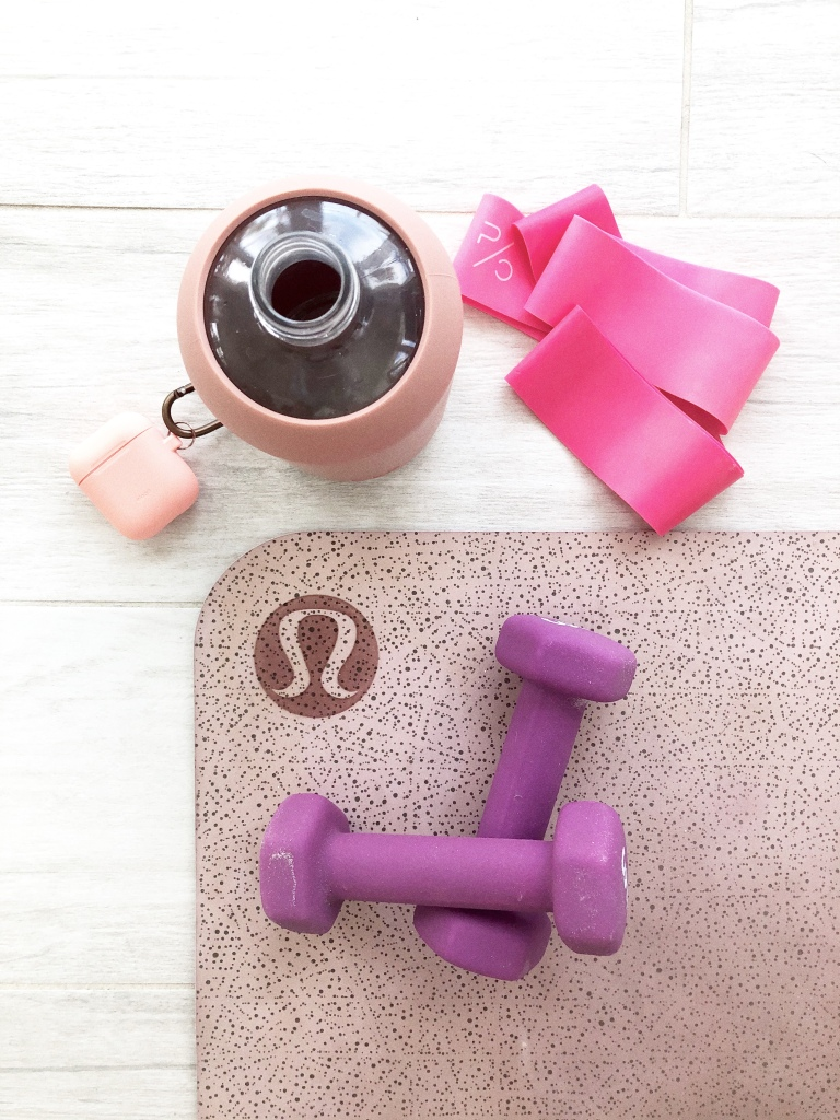 Yoga mat with weights, water bottle and other fitness accessories
